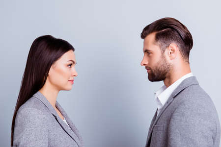 Foto de Concept of confrontation in business. Close up photo of two young serious confident people standing face-to-face to each other - Imagen libre de derechos