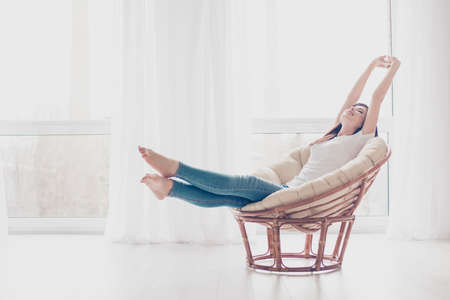 Photo pour Young girl is stretching in modern armchair in light livingroom. She is sleepy and dreamy, wearing casual clothes - image libre de droit