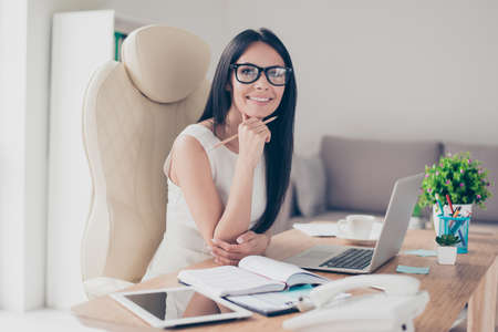 Photo pour Success conception. Portrait of gorgeous young businesslady in glasses sitting at her workplace in the office - image libre de droit
