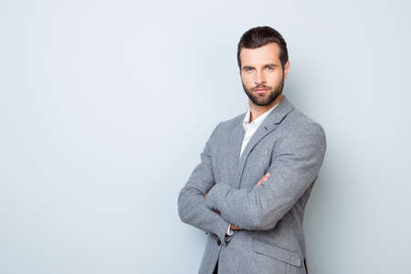 Photo for Portrait of handsome successful respected businessman in formal clothing standing with crossed hands against gray background - Royalty Free Image