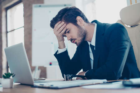 Photo pour Young tired, ill, overworked  man in formal wear sitting in front of computer and touching his forehead - image libre de droit