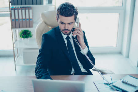 Foto de Serious minded young entrepreneur in black formal-wear with tie receiving calls and giving some advice about new project to his colleagues - Imagen libre de derechos