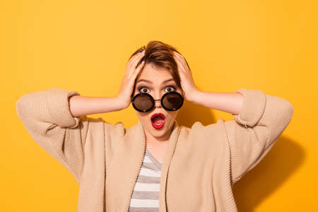 Photo pour No way! Close up portrait of shocked girl in stylish sunglasses and casual wear on the yellow background - image libre de droit