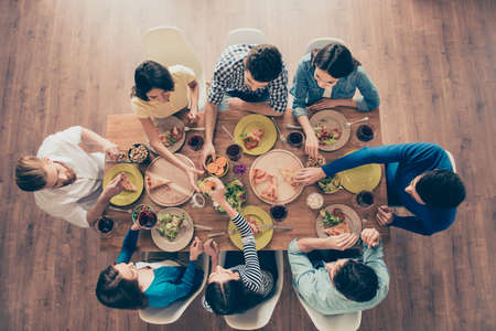 Foto de Top view of group of eight happy friends having nice food and drinks, enjoying the party and communication - Imagen libre de derechos