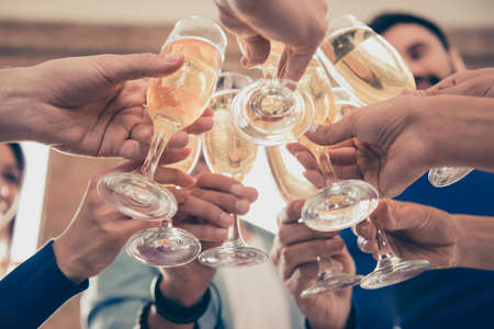 Foto per Cropped under view of friends cliking the glasses of bubbling champagne to celebrate an event together - Immagine Royalty Free