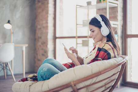Photo for Portrait of beautiful happy latin girl sitting in stylish armchair at home with phone and listen to music with white headphones, covered by blanket - Royalty Free Image