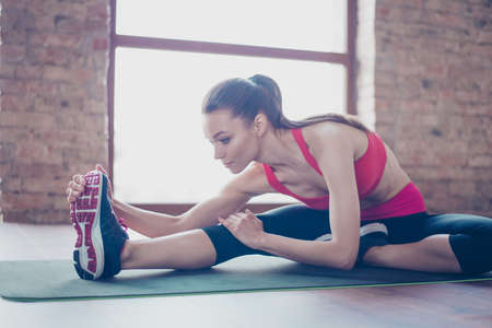 Photo for Focused young lady is doing her stretching to be bendy and flexible. She is wearing pink sportswear and stylish sneakers - Royalty Free Image
