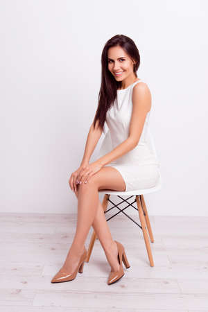 Photo pour Full size portrait of successful gorgeous lady. She is wearing formal white stylish dress and high hills shoes, sitting on a chair on pure background - image libre de droit