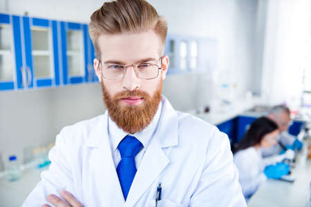 Foto de Close up portrait of young successful handsome red  bearded researcher, who is  in the lab, wearing formal wear and labcoat, glasses - Imagen libre de derechos