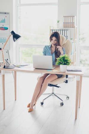 Foto de Full size photo of elegant business lady sitting in her office and browsing info in laptop. She is wearing formal wear and high hills - Imagen libre de derechos