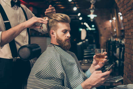 Photo pour Chill out at the barber shop. Side view of handsome young red bearded man drinking scotch and browsing at his pda, while getting a haircut - image libre de droit