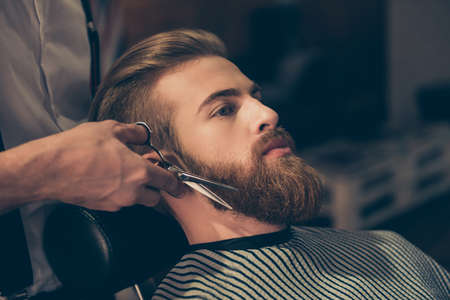 Photo pour Close up of a hairdresser`s work for an attractive young man at the barber shop. He is doing styling of a red beard with scissors - image libre de droit