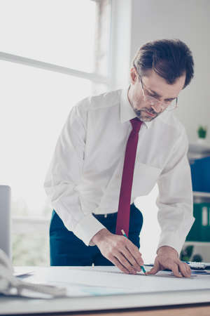 Photo for Businessman is drawing a scheme of new ideas foe startups. He is standing by the table, wearing shirt and tie, glasses - Royalty Free Image