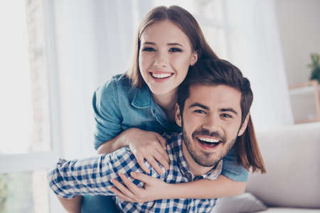Photo for Beautiful couple of young lovers are hugging indoors at home, looking at the camera, wearing casual clothes - Royalty Free Image