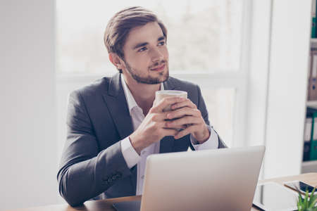 Photo for Young dreaming worker is thinking in front of laptop at work place. He is happy, smiling and holding a cup of coffee - Royalty Free Image