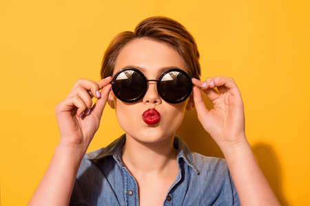 Foto de Fashionable young cute girl in trendy sunglasses sends a kiss against bright yellow background, she holds spectacles with her hands - Imagen libre de derechos
