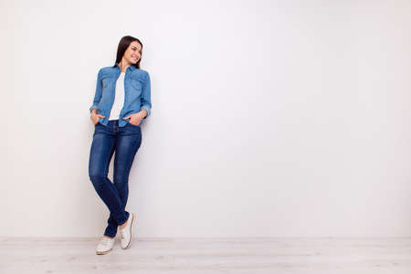 Photo for Full-length portrait of beautiful smiling woman holding hands in pockets and leaning on white wall - Royalty Free Image