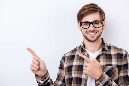 Photo pour Successful student in a brown checkered shirt and glasses with bristle is showing the copy space on pure white background - image libre de droit