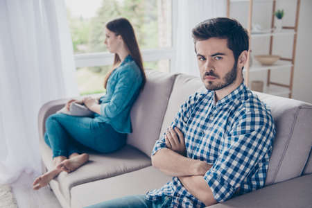 Foto de Annoyed couple is ignoring each other, sitting on the couch indoors at home with sad faces - Imagen libre de derechos