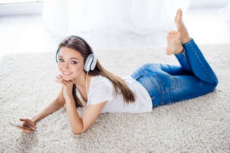 Photo for Pretty young lady is listening to the music with headphones at home lying on the white carpet - Royalty Free Image