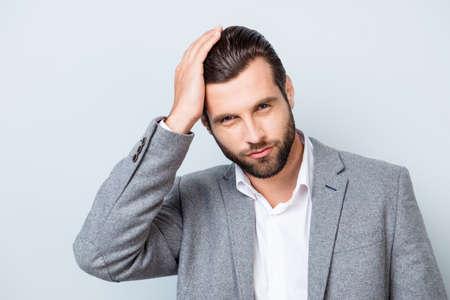 Foto de Close up portrait of handsome young confident man in gray suit touching his perfect hair - Imagen libre de derechos