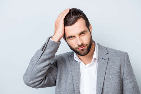 Photo pour Close up portrait of handsome young confident man in gray suit touching his perfect hair - image libre de droit