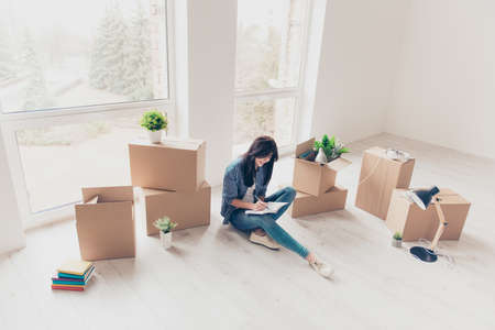 Foto de Home, sweet home! Young girl in casual clothes is sitting with crossed legs on the floor of her new apartment. She just moved in, writing about her feelings in diary. A lot of unpacked boxes near her - Imagen libre de derechos