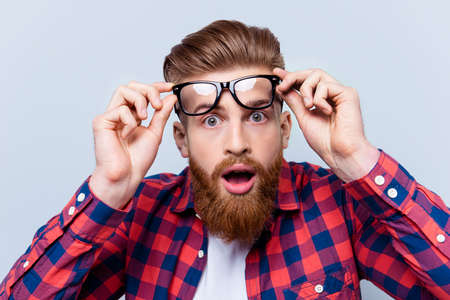 Foto de It's incredible! Close up portrait of young bearded man touching the spectacles and keeping his mouth open against gray background - Imagen libre de derechos