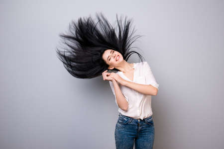 Photo for Dreamy brunette in casual outfit is is so happy with closed eyes, her hair is flying in the air, she stands on a pure grey background - Royalty Free Image