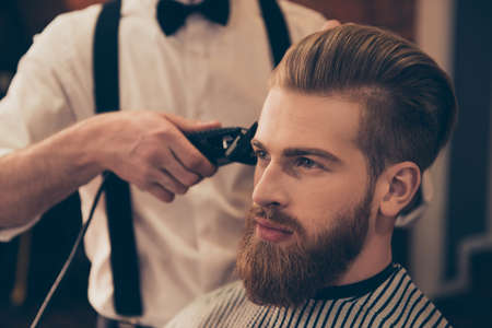 Foto de Close up of a hairdresser`s work for a handsome young guy at the barber shop. He is doing styling with the electric shaver - Imagen libre de derechos
