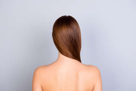 Foto für Close up cropped back view photo of young brown haired girl standing on light blue background. She has a healthy and shining skin and hair - Lizenzfreies Bild