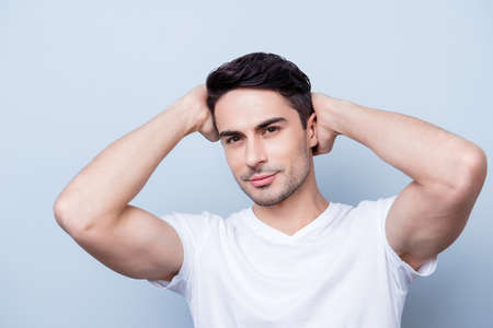 Foto de Confident smiling handsome young man in white t shirt. standing on the pure background, fixing his perfect hairstyle. So hot and attractive, harsh and fashionable - Imagen libre de derechos