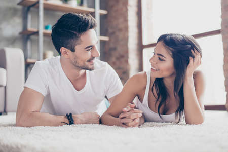 Photo for Together forever. A couple of young beautiful lovers are lying on the beige cozy carpet indoors at home, holding hands and looking deep into eyes of each other with love and tenderness - Royalty Free Image