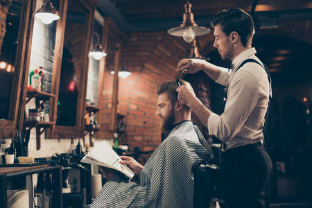 Foto de Low angle profile view of red bearded stylish barber shop client, which is getting his perfect  haircut from a classy dressed stylist, reading the magazine and waiting for result - Imagen libre de derechos