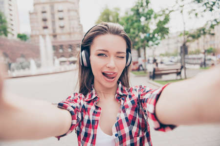 Foto de Selfie time! Young funky blogger is making photo for her social networks page, she is posing in a casual spring outfit and head phones, on the street in town - Imagen libre de derechos