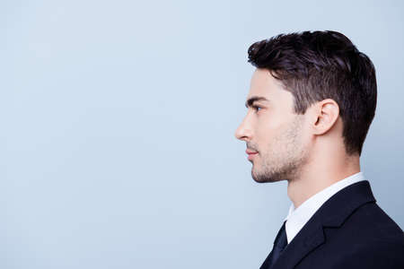 Photo pour Side profile photo of a young handsome brunete realtor with bristle in a formal wear, standing on the pure blue background next to copyspace - image libre de droit