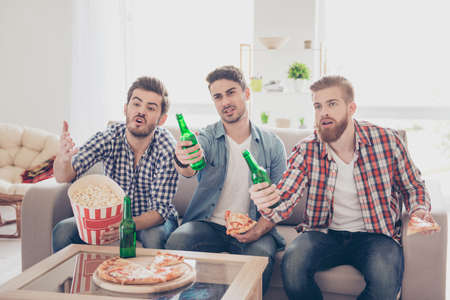 Foto de Upset young bearded guys are frustrated about the loss of the team in game they are watching. They are fans of sports games as football, basketball, hockey, baseball - Imagen libre de derechos