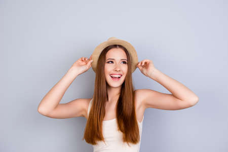 Photo pour Happy young girl on summer vacation. She is in a stylish hat, wearing casual singlet, holding her beige cap, amazed, on pure light background - image libre de droit