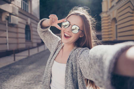 Photo for Cute young smiling girl is making selfie on a camera while walking outdoors. She is wearing casual outfit, mirror glasses - Royalty Free Image