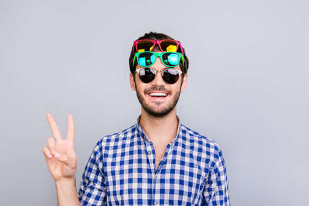 Foto de Playful young brunette bearded man in three pairs of bright colorful glasses and checkered casual shirt is fooling around, posing and shows v sign, smiling on light background - Imagen libre de derechos