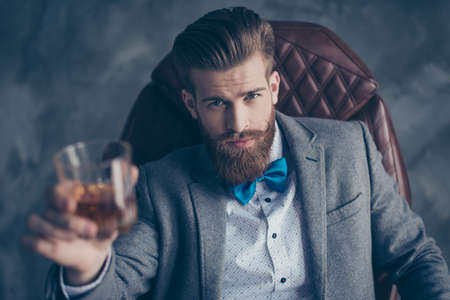 Foto de Cheers, ladies and gentlemen! Stylish elegant red bearded aristocrat in suit and bowtie holds glass with brandy, relaxing, sits on leather brown arm chair indoors - Imagen libre de derechos