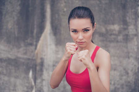 Photo pour Close up portrait of attractive serious fit boxer, ready for fight, on concrete wall background, wearing pink fashionable sport wear - image libre de droit