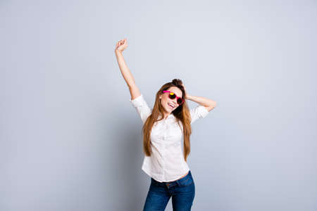 Photo pour Young cheerful  attractive girl in white shirt and jeans, pink sun glasses is standing on pure grey background in pose and touch her nice hair - image libre de droit