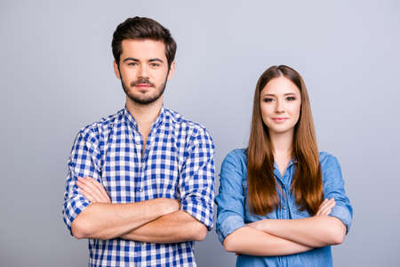 Foto de Two cheerful young lovers are looking at the camera and smile, standing both with crossed hands, wearing casual clothes, on the pure background - Imagen libre de derechos