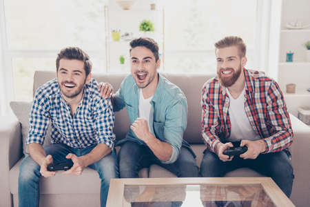 Foto de Yes! Our team is winning! Competition of guys playing car race. Three excited friends are playing games indoors, sitting on cozy beige sofa and enjoying themselves. They have great and fun time - Imagen libre de derechos