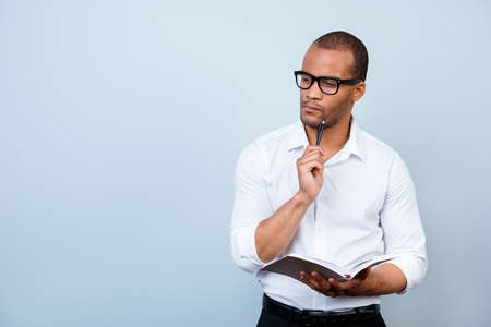 Photo for Nerdy academic african professor is thoughtful, in glasses, holding a notebook and thinking about exams - Royalty Free Image
