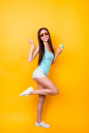 Foto de Full length of funky young korean lady is posing for vacation photo shot, wearing tourist`s outfit, glasses, holds ice cream. Happiness, dream, fun, joy, freedom concept - Imagen libre de derechos
