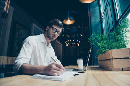 Foto de Young stylish well dressed author writer is working in a modern coworking, writing the novel, in glasses, so serious and focused - Imagen libre de derechos