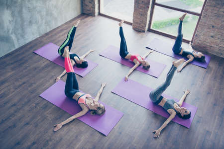 Photo pour Left-right! Topview of spinal twist, five young sporty women are doing in modern studio, lying on purple mats. Hands on the wooden floor, legs up - image libre de droit