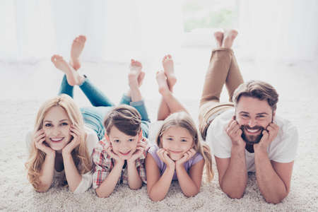 Photo pour High angle view of happy family of four relatives, lying with crossed legs on the beige carpet on the floor, holding heads with arms, smiling, at home - image libre de droit